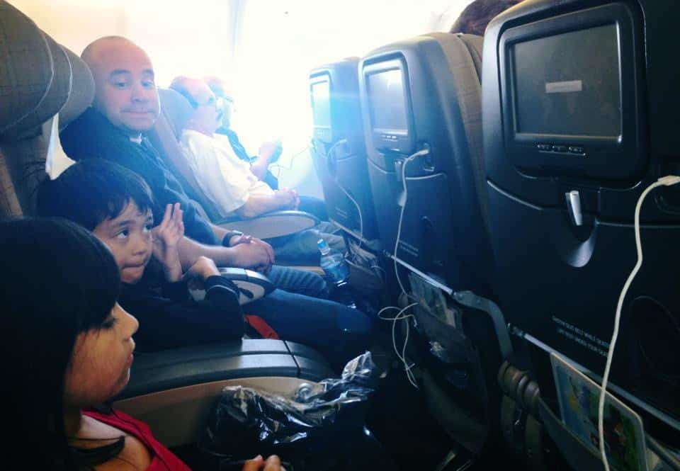daughter and son on a plane watching tv