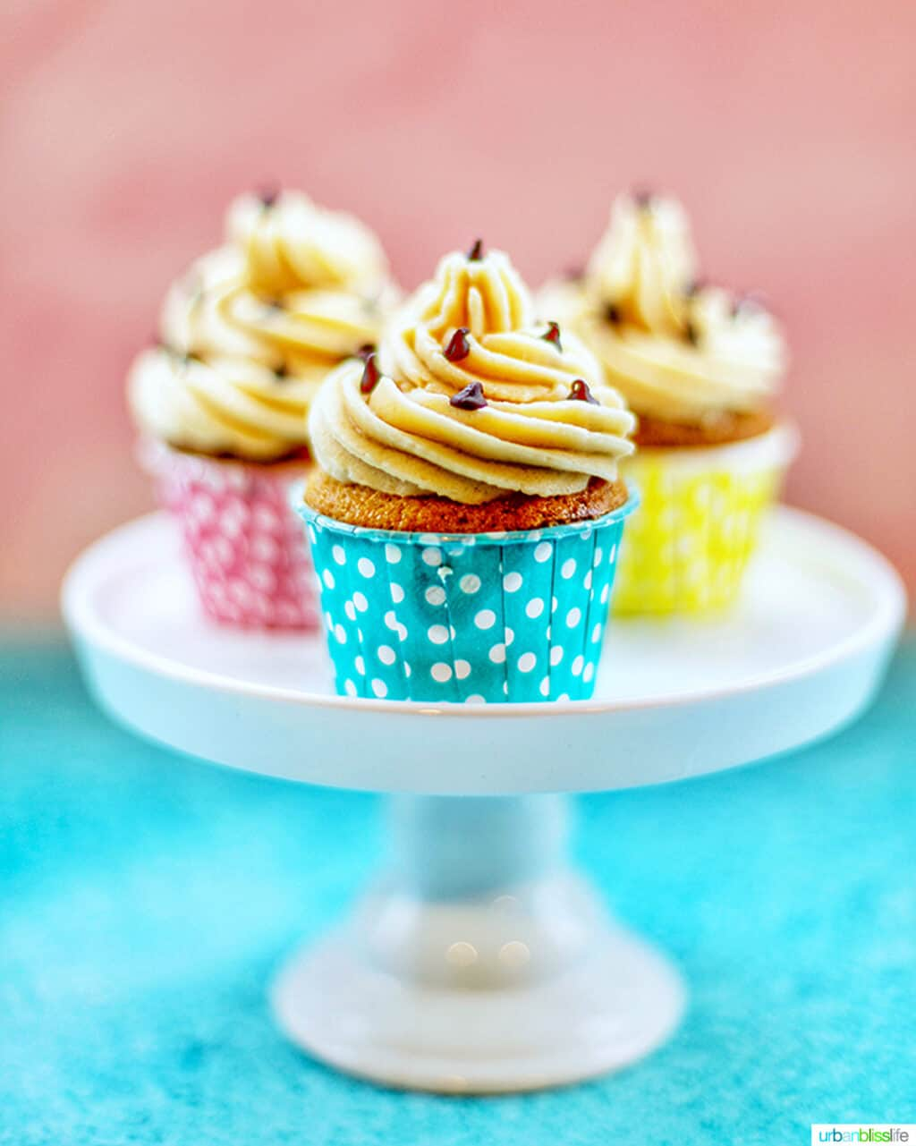 trio of chocolate chip cupcakes with cookie dough frosting in colorful polka dot baking cups on a white pedestal