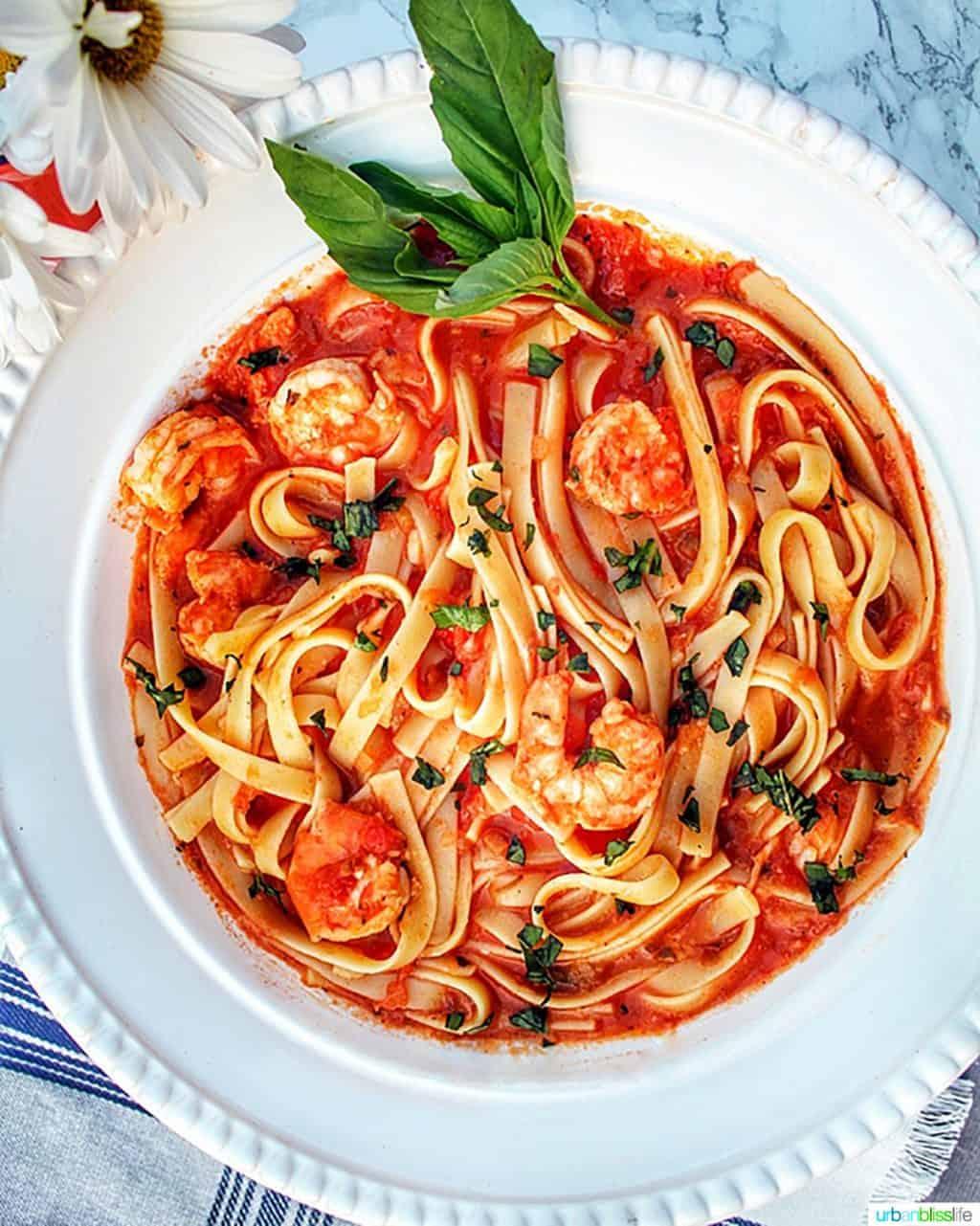 bowl of shrimp fettuccine with sprig of basil