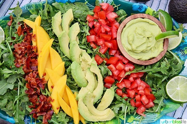 sliced avocados, mangos, tomatoes, and chopped bacon with avocado lime dressing