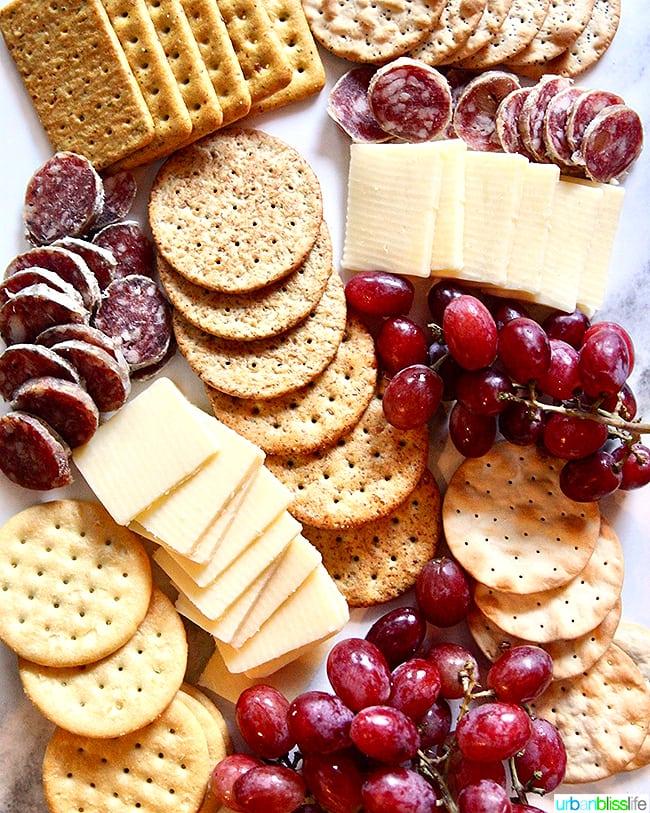 cheese, crackers, salami, and grapes