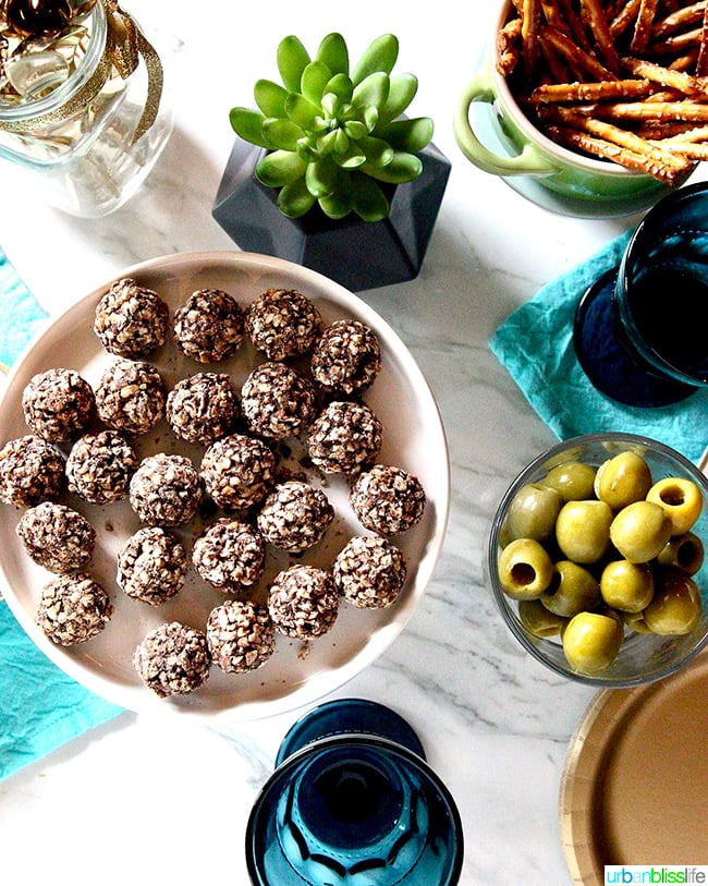 holiday party table with olives, chocolate truffles, and pretzels