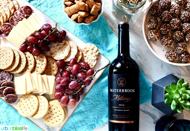 holiday party table with cheese, crackers, and Waterbrook wine
