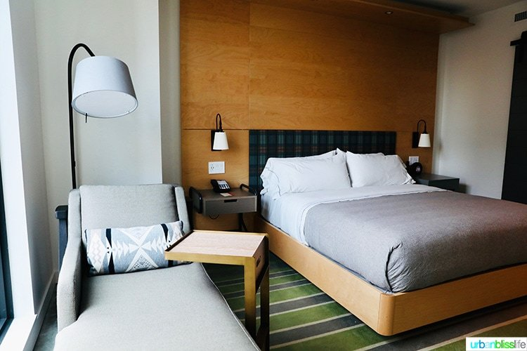 guest room bed & window seat in Canopy by Hilton Portland hotel