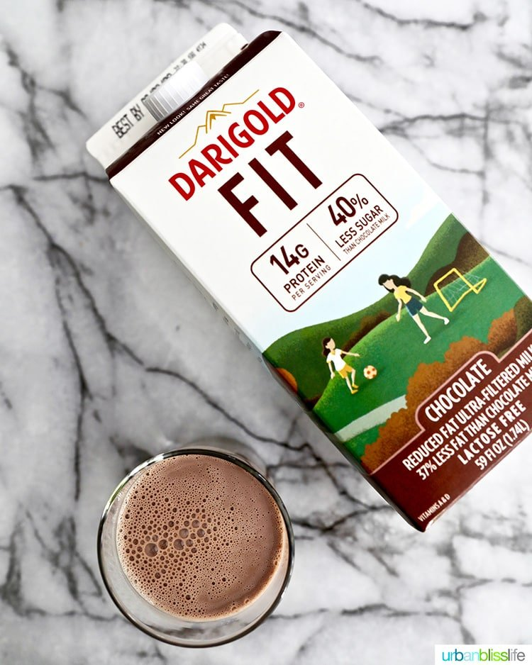 glass of ultrafiltered chocolate milk with carton of Darigold FIT chocolate milk