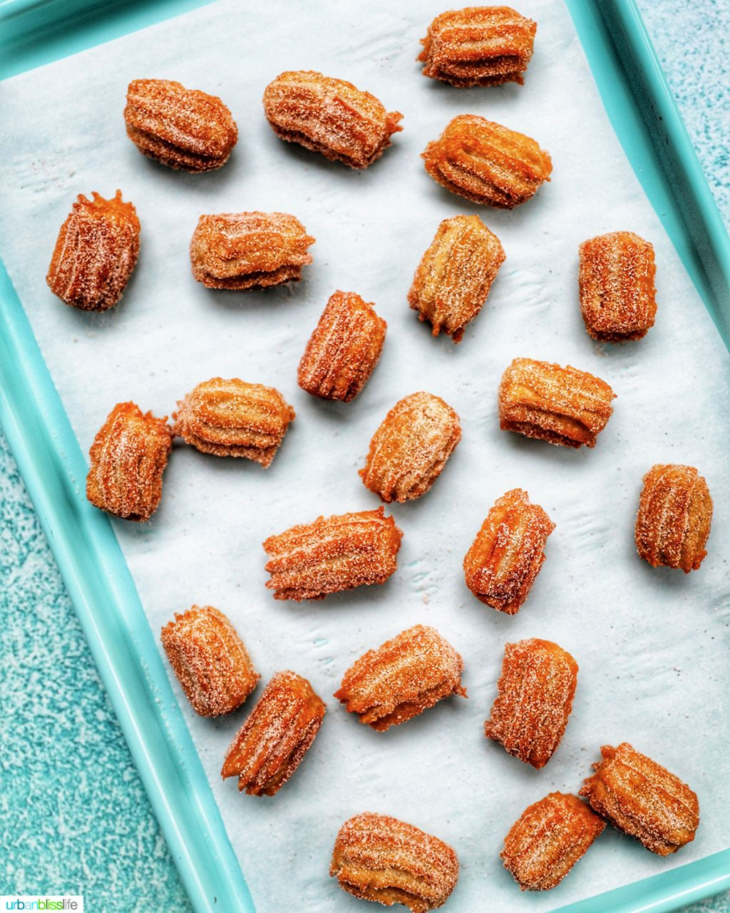 churros sprinkled on a baking tray