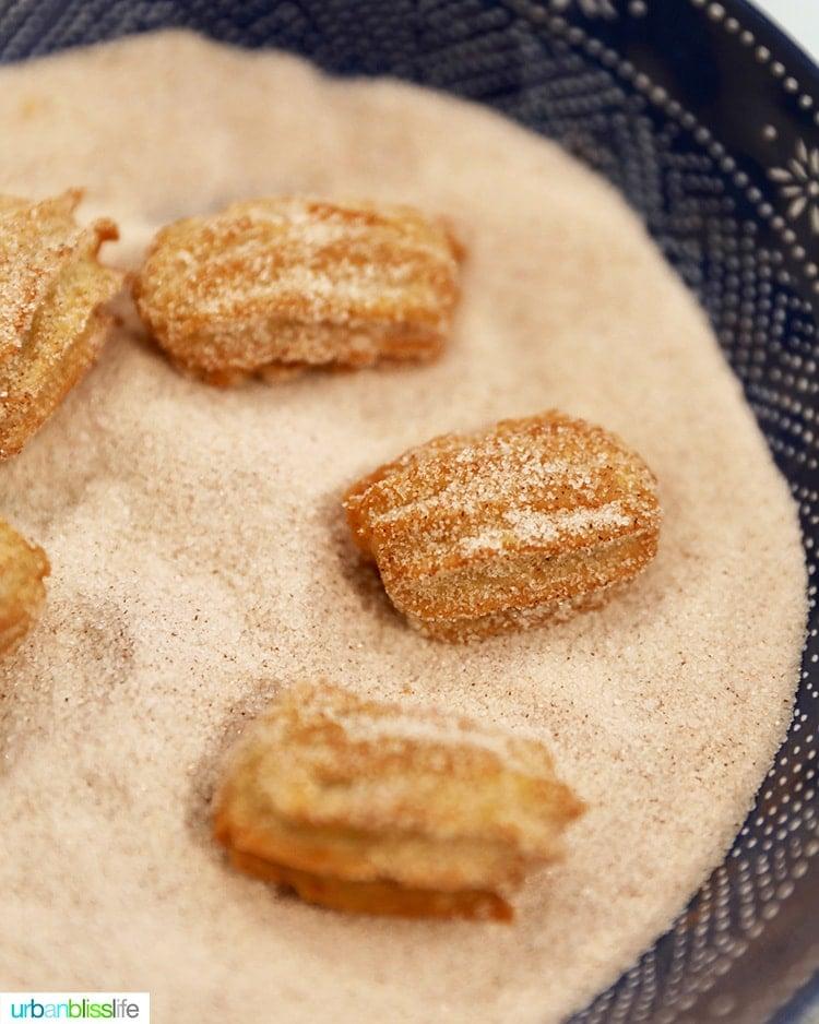 coating churros with cinnamon sugar