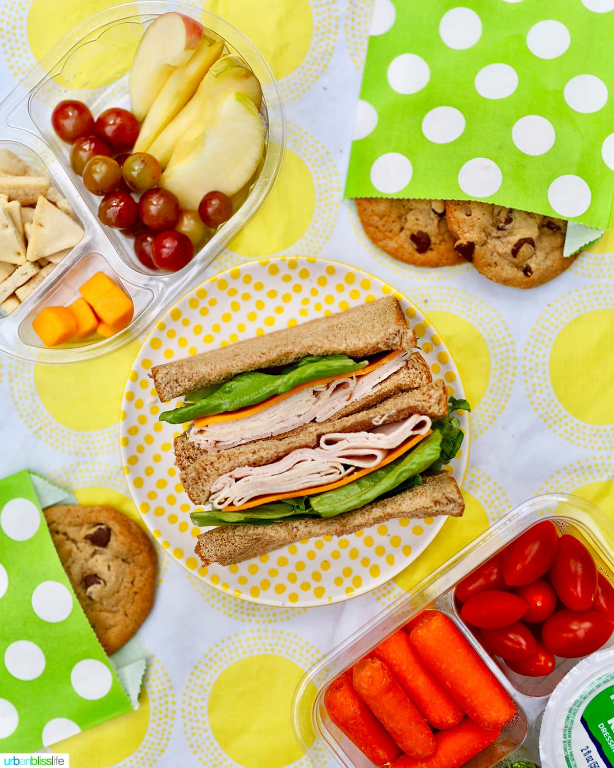 back to school lunches - sandwiches, cookies, cheeese, fruit, vegetables against yellow and white tablecloth