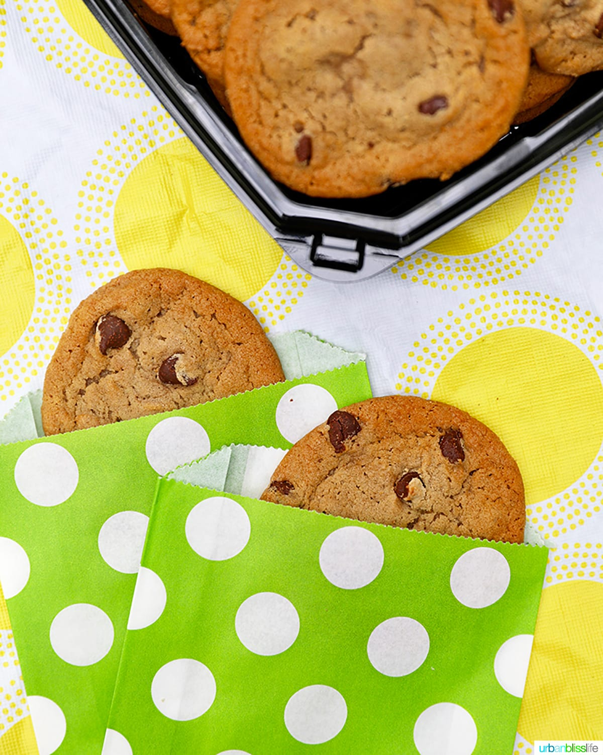 chocolate chip cookies in cute bright green paper sleeves against yellow and white tablecloth
