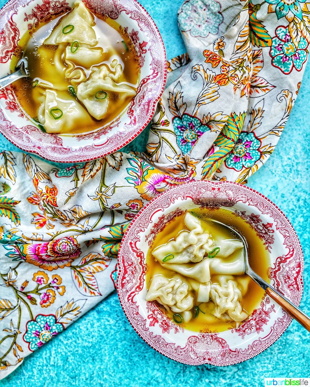 two bowls of wonton noodle soup with spoon, colorful napkin, and blue background