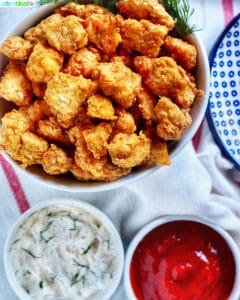 air fryer popcorn chicken in bowl with two sauces