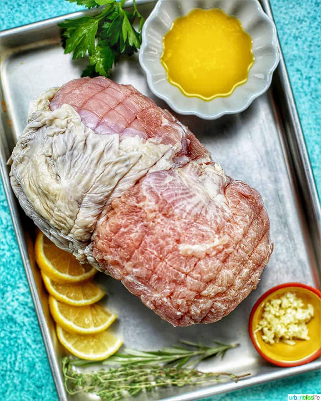 turkey breast ingredients on baking sheet against blue backdrop
