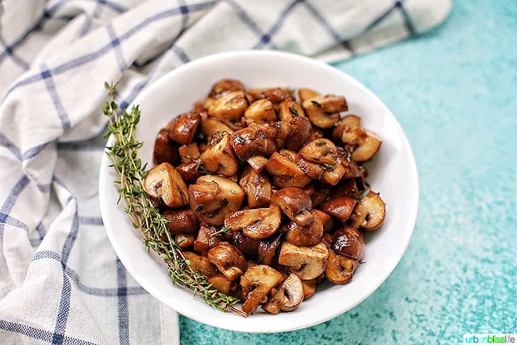 bowl of mushroom marsala with blue background and kitchen towel