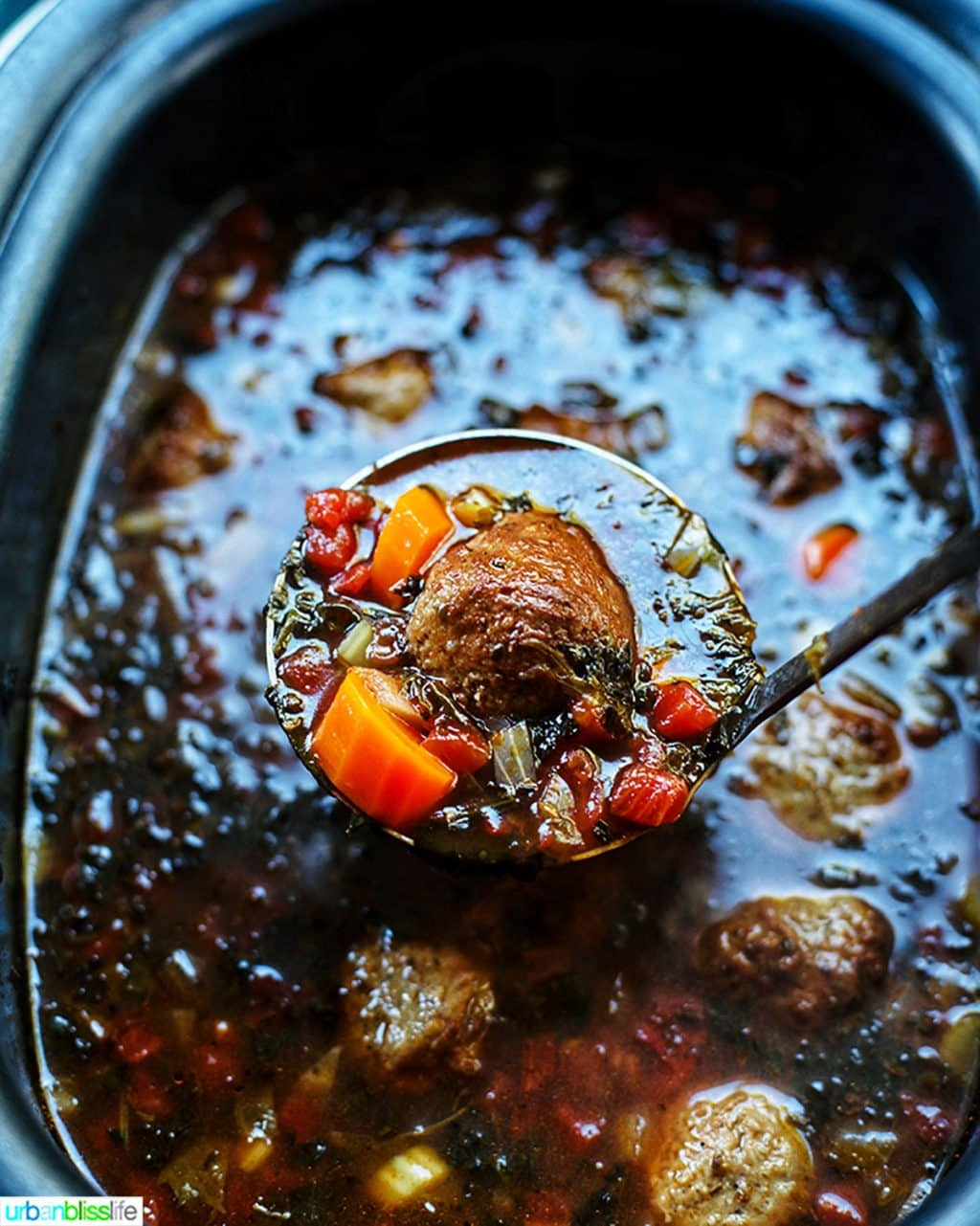 spoonful of meatball soup in slow cooker