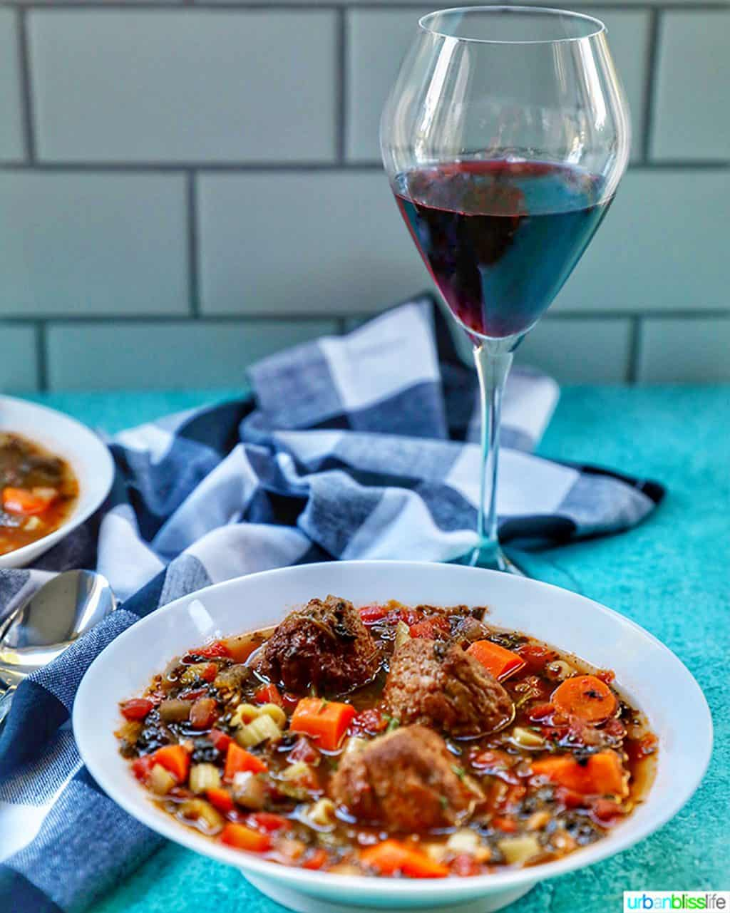 glass of red wine with bowl of meatball soup