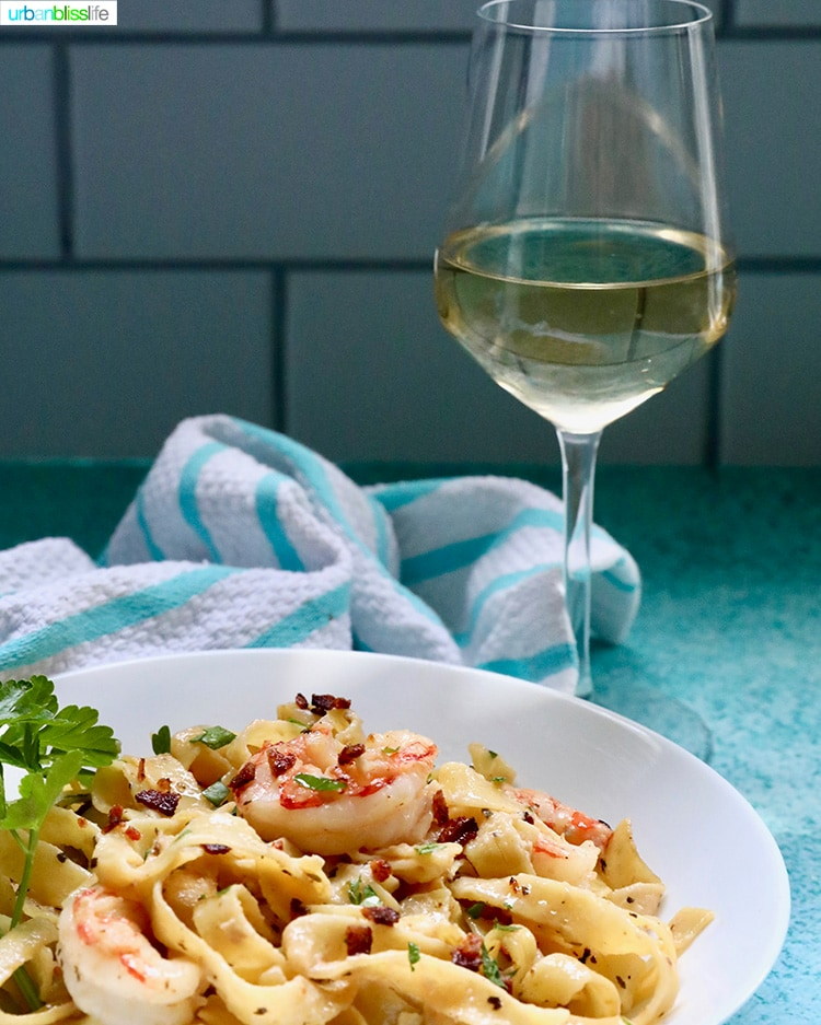 shrimp pasta with glass of white wine