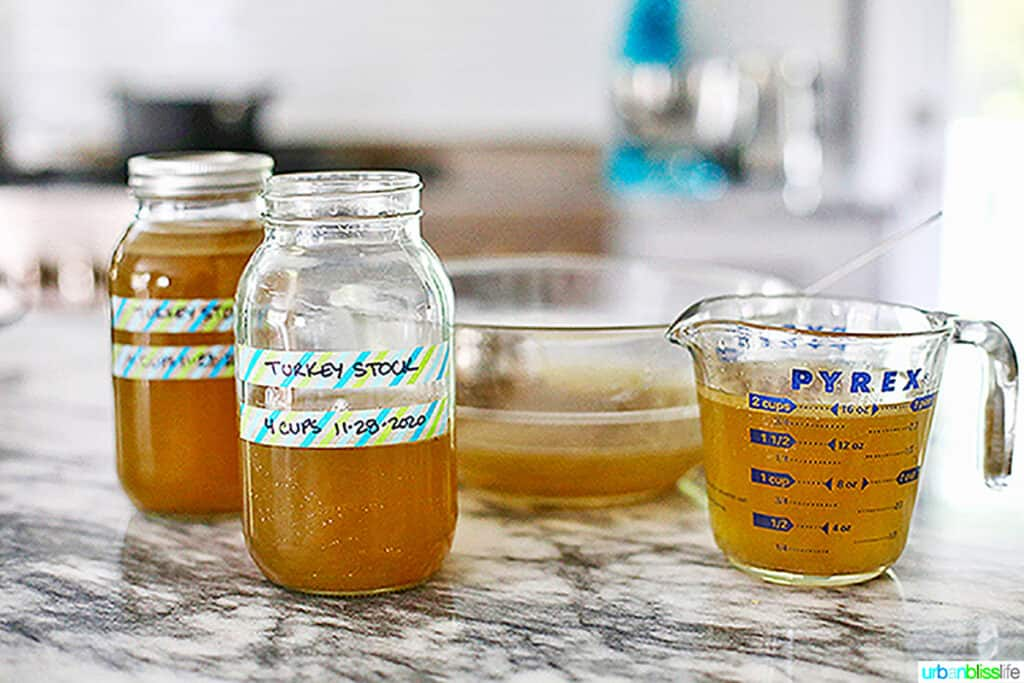 homemade turkey stock in measuring cup and mason jars labeled
