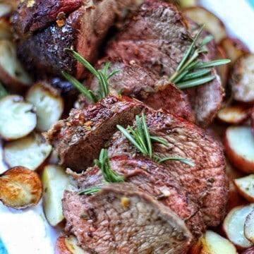Garlic Rosemary Sirlopin Tip Roast sliced on platter with potatoes