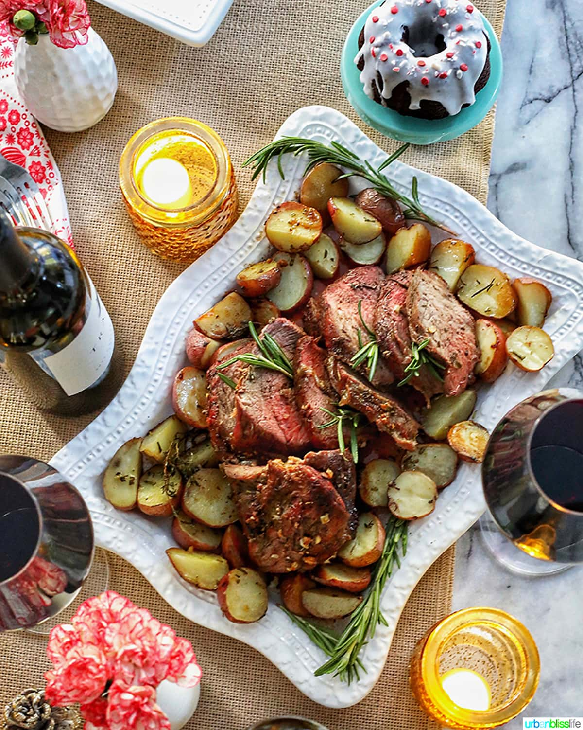 beef roast on white platter with wine glasses and candles