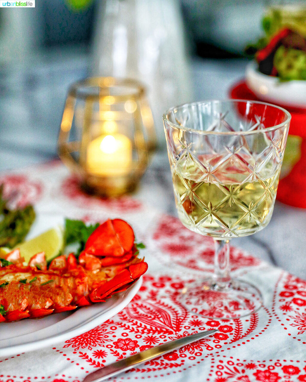 white wine with lobster tail and candle in the background