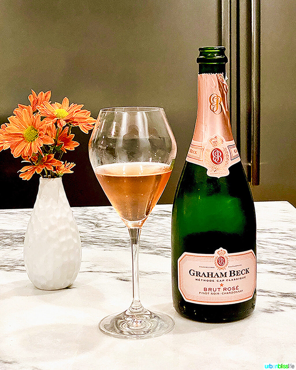 graham beck brut rose bottle, glass, and flowers