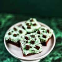 Mint Chocolate Chip Brownies on a cake pedestal on green background