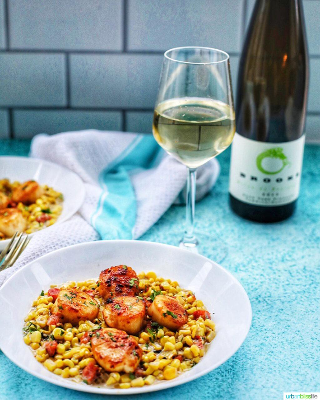 Seared scallops with corn and white wine in a glass and bottle