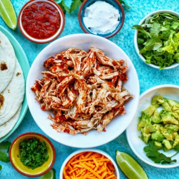 Instant Pot Salsa Chicken with salsa, sour cream, cheese, and other toppings for tacos