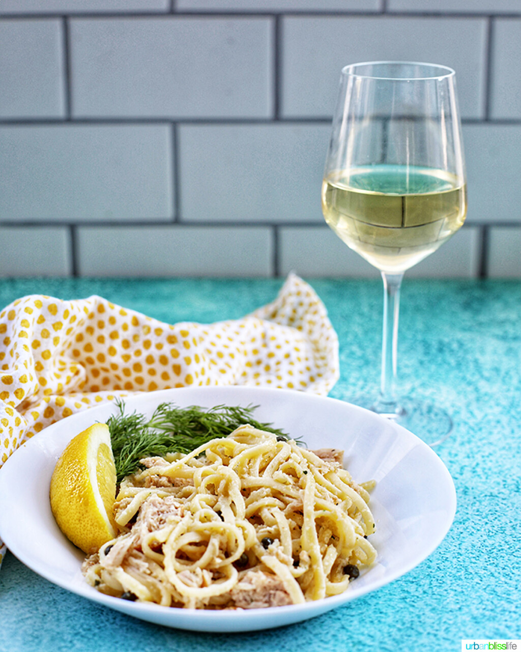 glass of white wine with bowl of tuna pasta