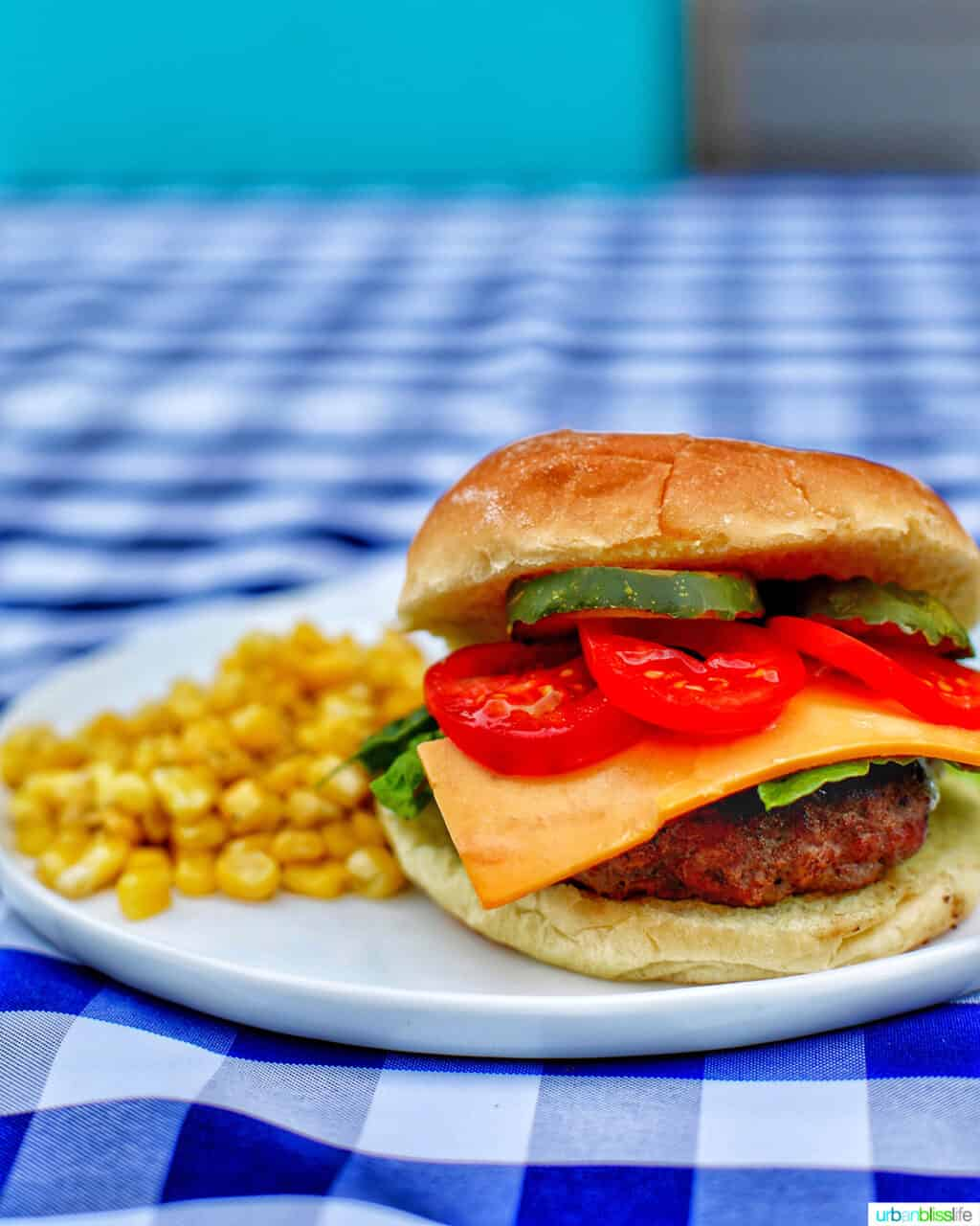 burger and side of corn on checkered tablecloth