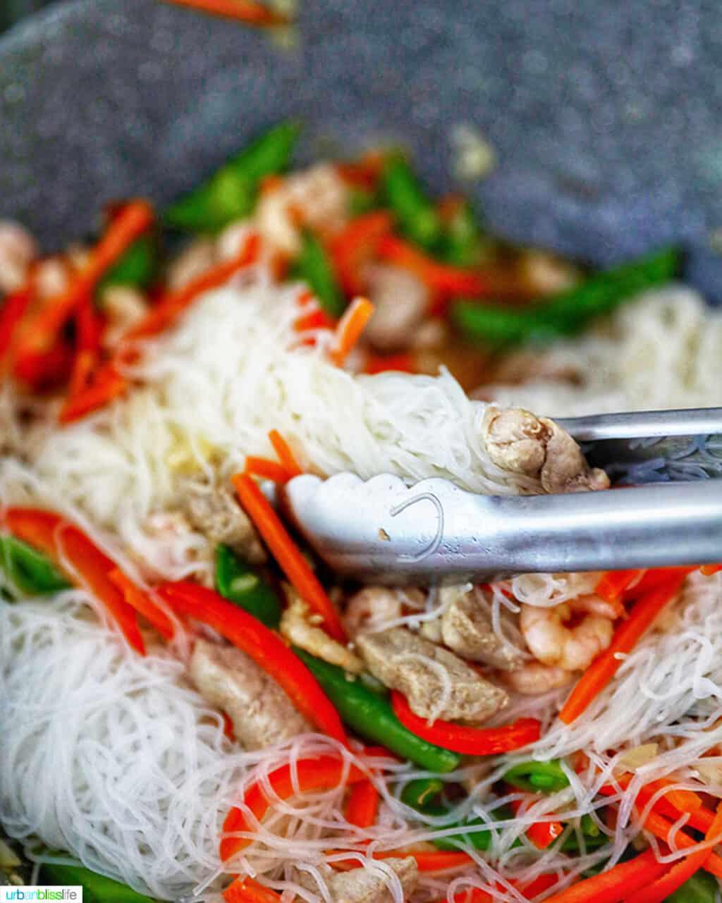 tongs mixing noodles into Filipino Pancit Bihon