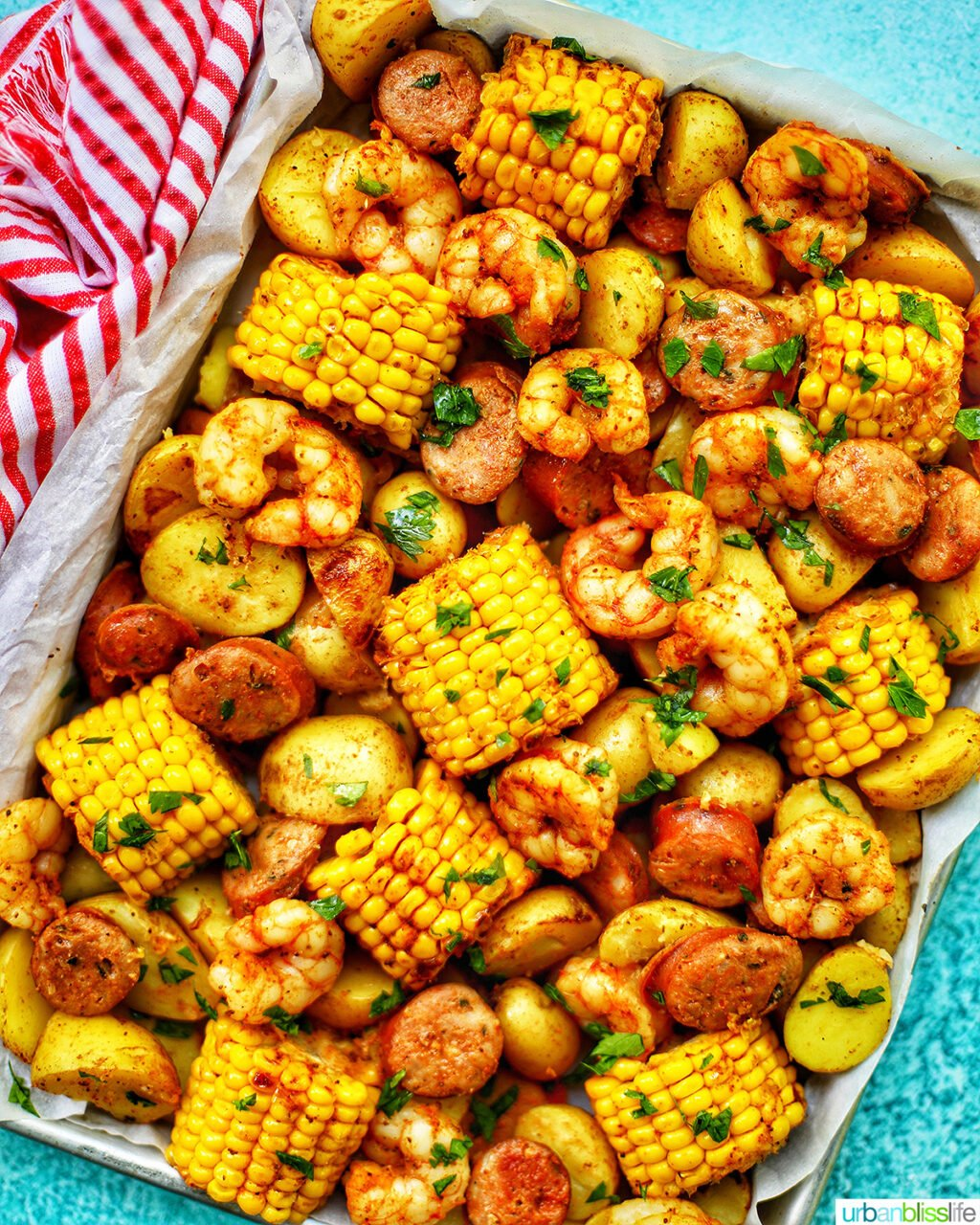 tray of seafood, corn, sausage low country boil with blue background and red and white towel