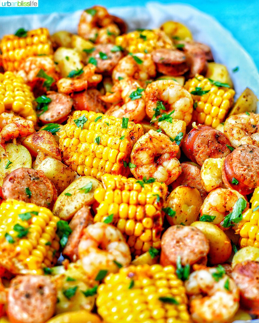 tray of seafood, corn, sausage low country boil with blue background