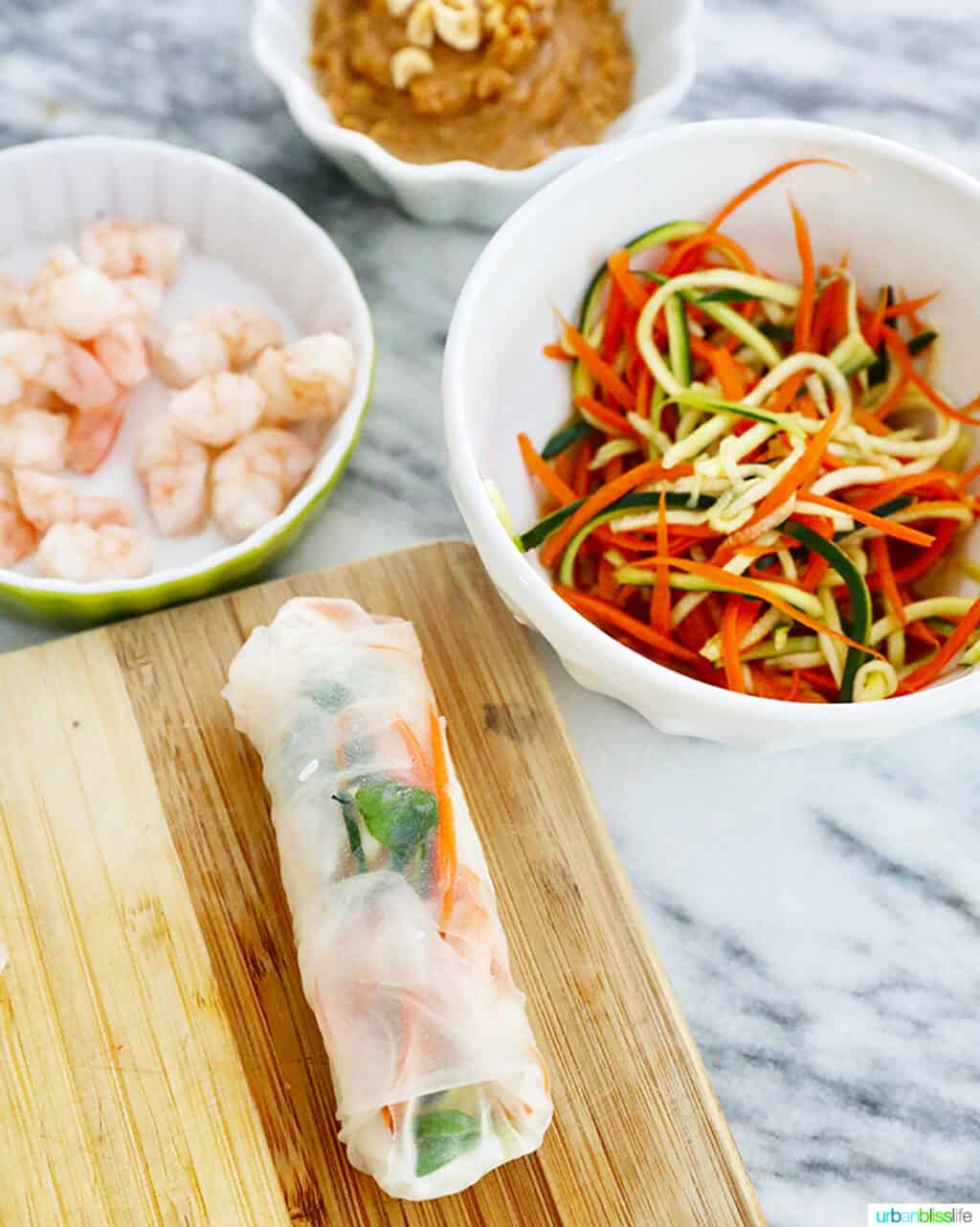 one shrimp roll assembled with ingredients in bowls