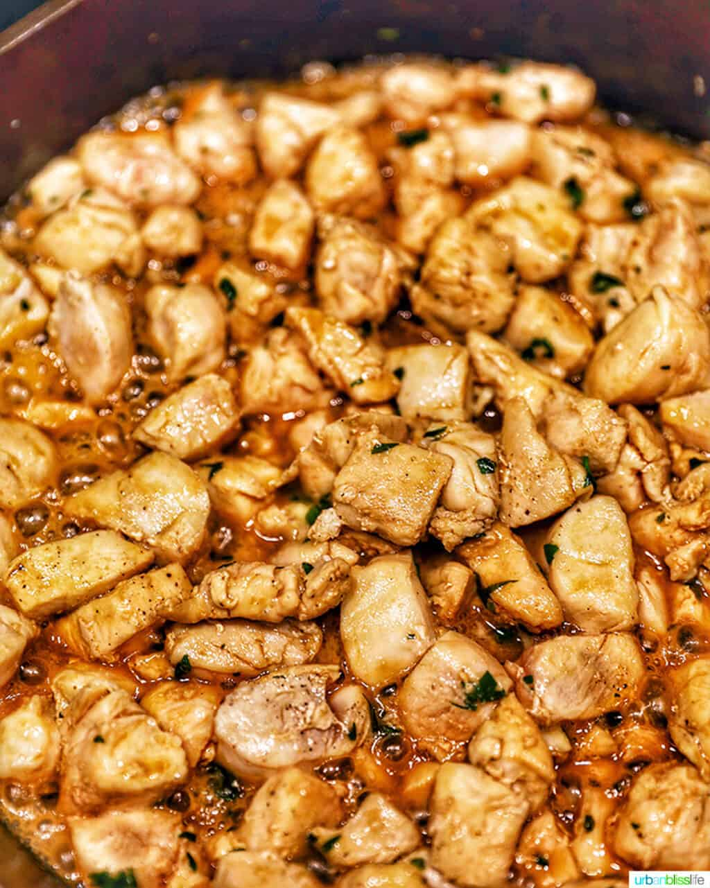 soy garlic butter chicken bites cooking in a cast iron pan