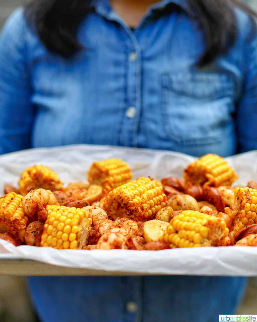 holding a tray of low country seafood boil foil packets against denim shirt