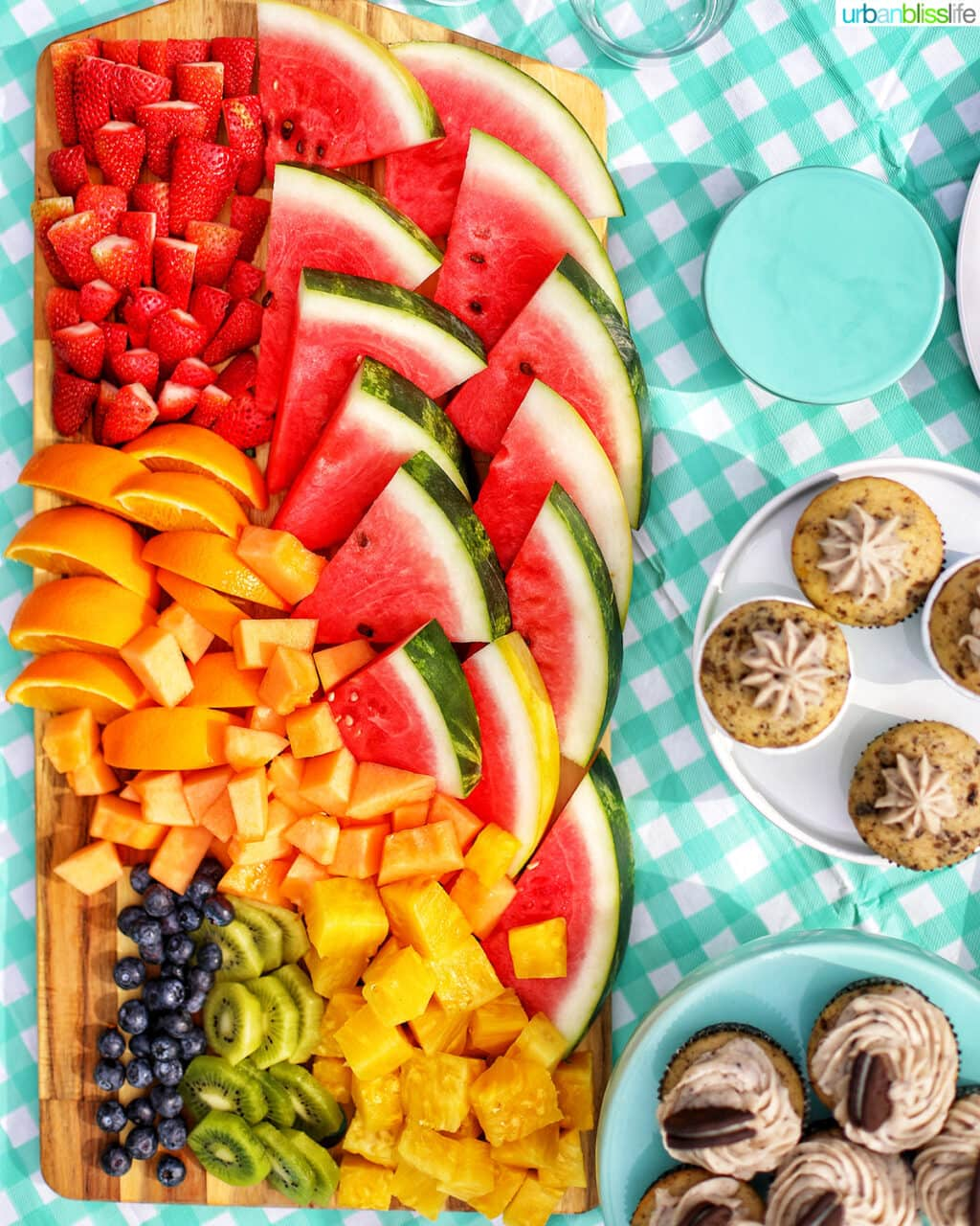 large fruit platter on an aqua checkered tablecloth with side of cupcakes