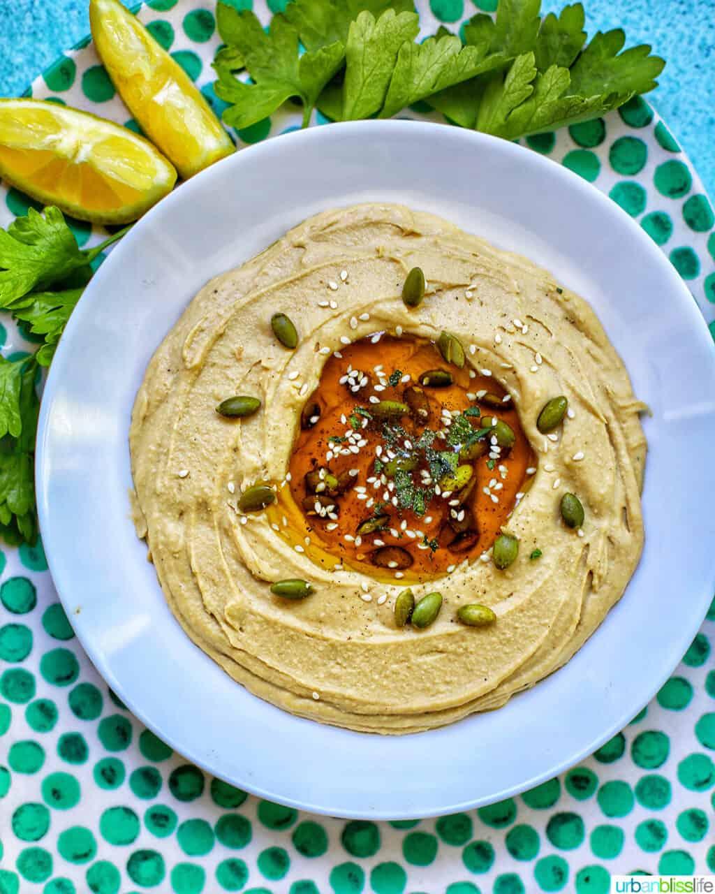 hummus in a white bowl on green polka dot platter with lemon slices