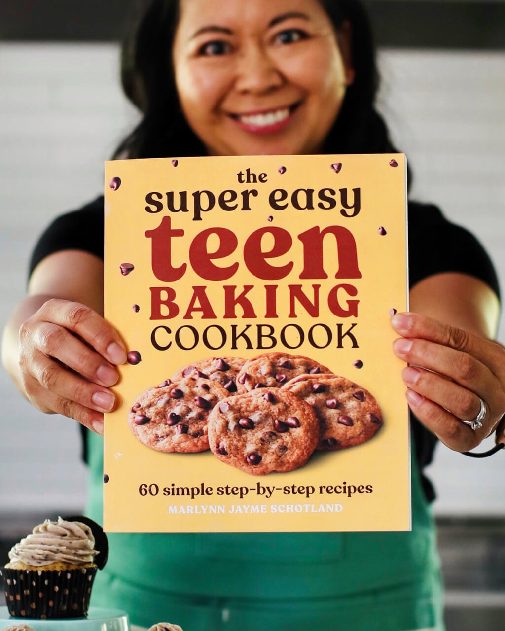 Marlynn holding out Super Easy Teen Cookbook