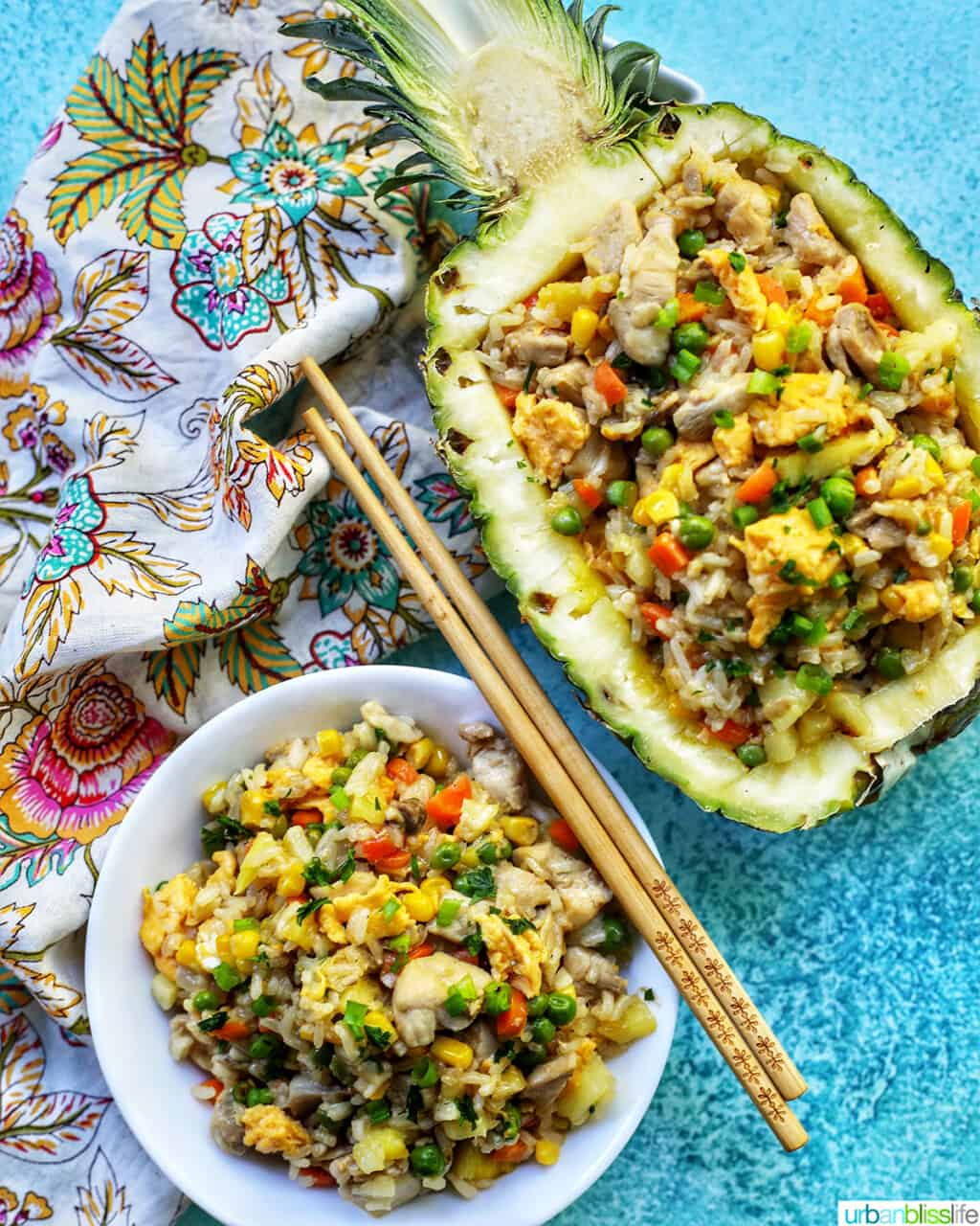pineapple fried rice in hollowed out pineapple boat with bowl of fried rice