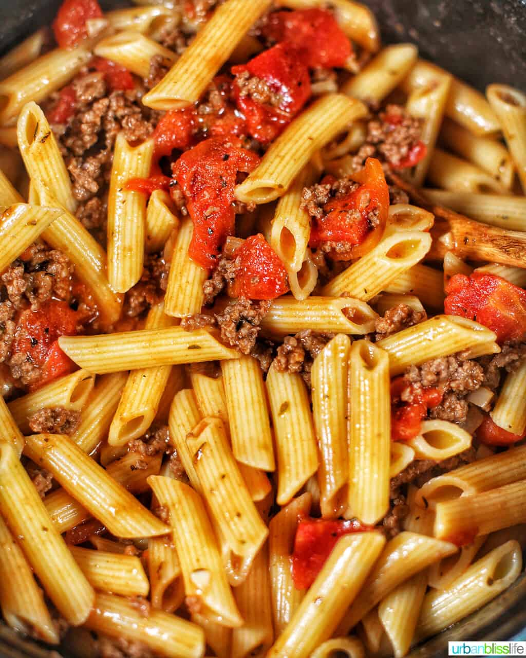 mixing pasta with meat sauce