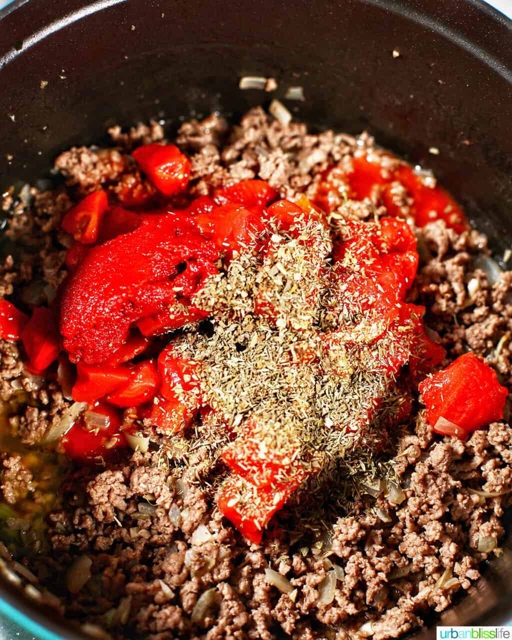 adding tomato paste and herbs to ground beef