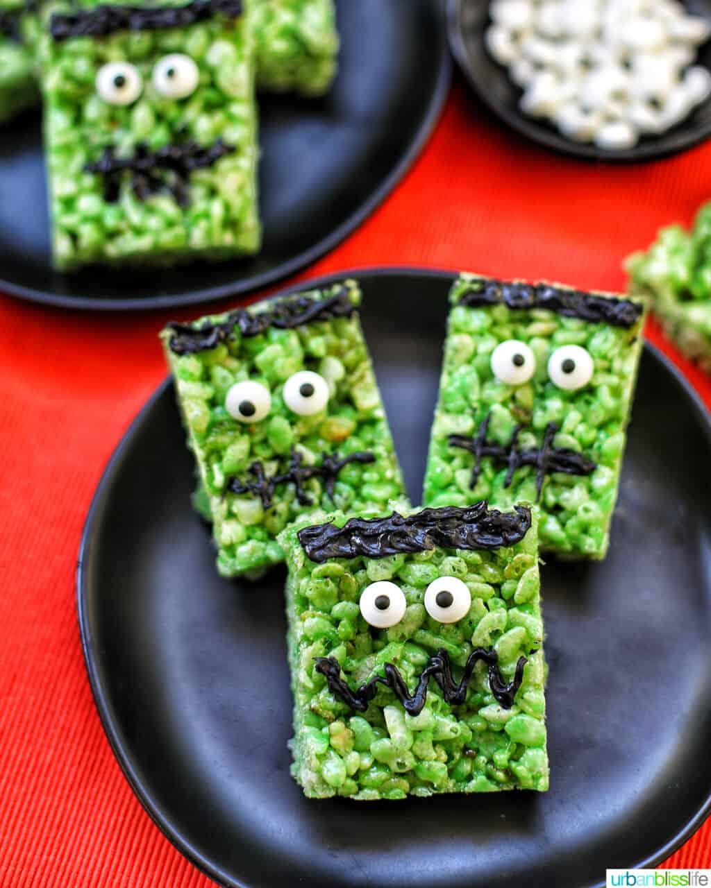 Frankenstein Rice Krispie Treats on top of black plates and orange background