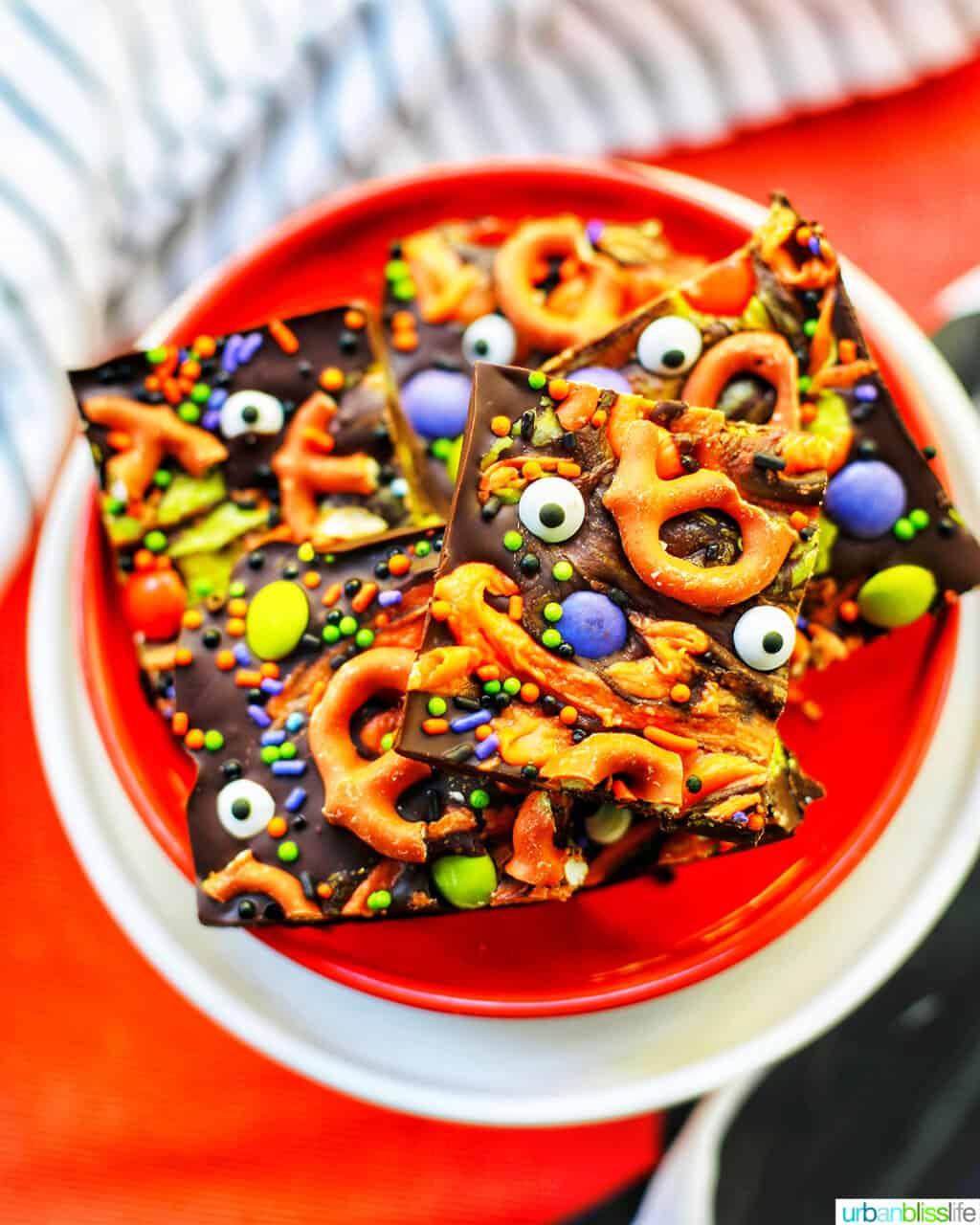Monster Halloween Bark squares on orange and white plates