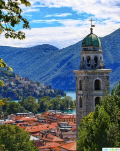 church steeple, clay rooftops, and mountains of Lugano, Switzerland