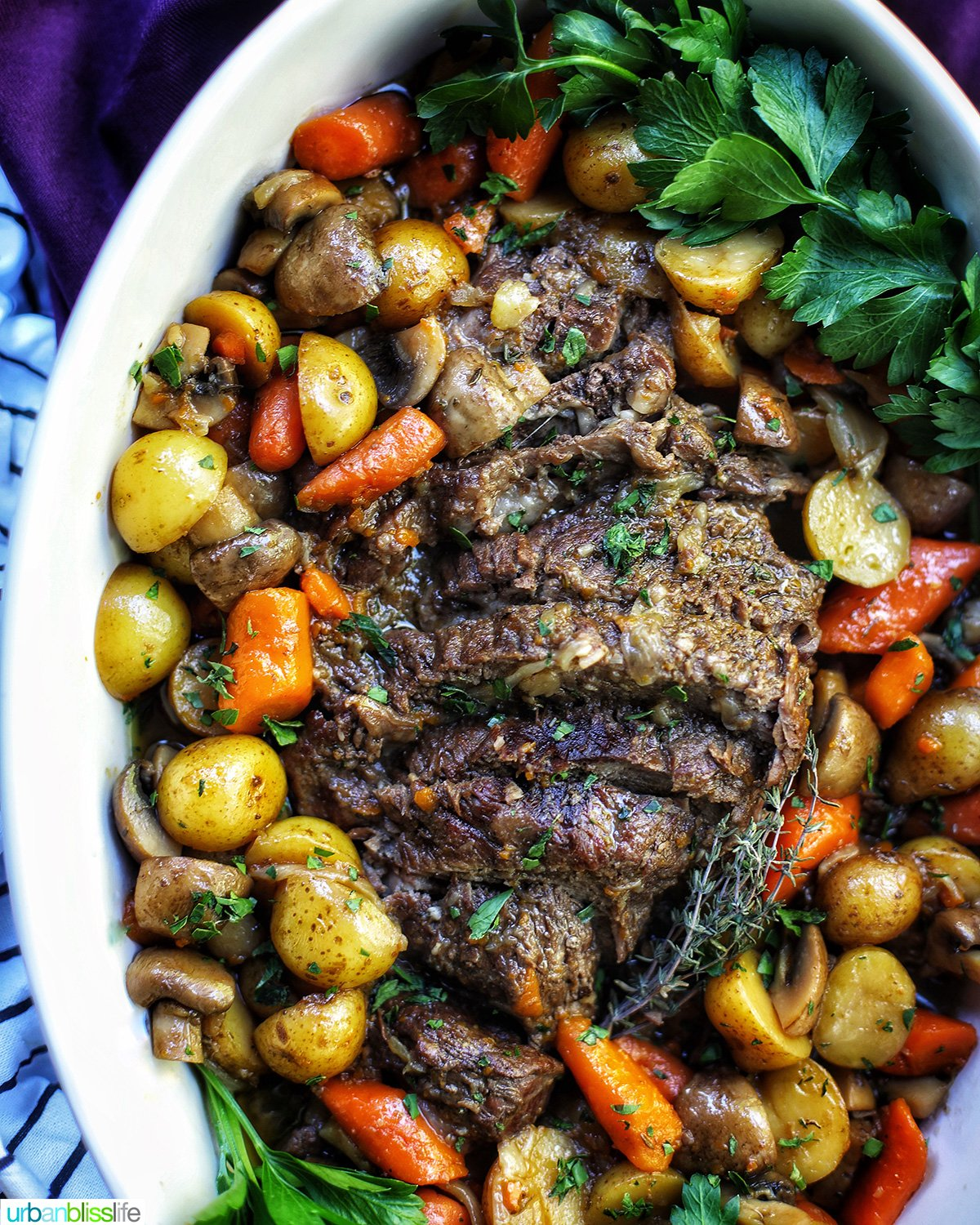 dutch oven pot roast with vegetables in a large white serving platter